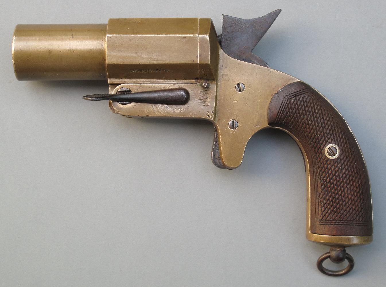 C'est finalement un pistolet de fabrication rustique et peu onéreuse, copié sur les modèles déjà existants, qui sera adopté et produit à la hâte au moment des hostilités. Ce pistolet signaleur à canon court (Gazette des Armes N°485) présente l'avantage d'être robuste en raison de son extrême simplicité et sa fabrication en bronze le met à l'abri de la corrosion.