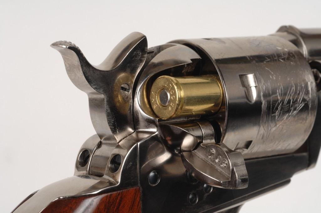 Introduction de la cartouche, le long du couloir d'alimentation. On notera que le barillet a conservé sa gravure, appliquée à la molette sur toute sa circonférence. Cette gravure commémorait la bataille navale du 16 mai 1843 remportée sur les Mexicains par les Texans, dont les marins étaient armés de revolvers et de carabines Colt Paterson.
