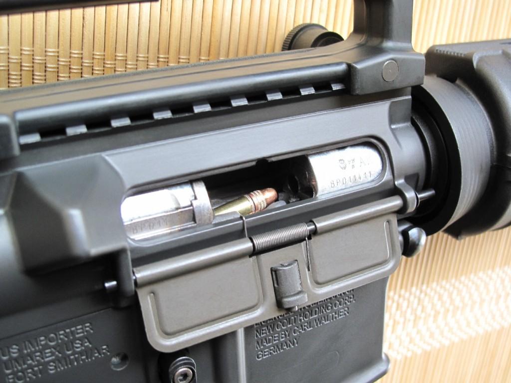 Le volet en tôle d'acier emboutie qui permet, sur le fusil d'assaut M16, d'obturer la fenêtre d'éjection pour éviter que les projections de sable ou de boue n'y pénètrent est bien présent, mais son système de verrouillage n'est pas véritablement opérationnel sur cette copie en calibre .22 Long Rifle.