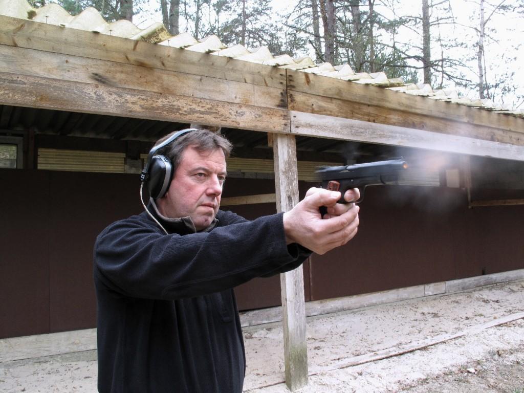 Cette photo, prise au moment où la balle vient tout juste de quitter le canon, permet d'observer la flamme à la bouche, la fumée qui s'en dégage et l'amorce de recul de la culasse à glissière.