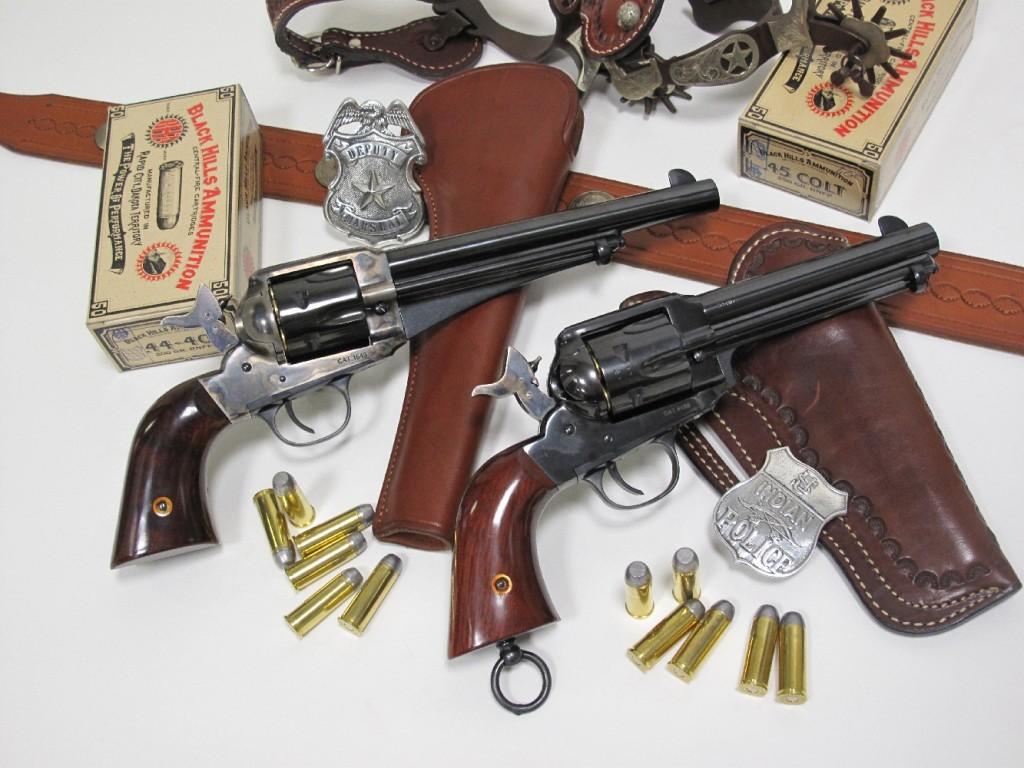Les deux revolvers Remington Single Action Army modèle 1875 et modèle 1890 (répliques réalisées par la firme italienne Aldo Uberti) accompagnées de leurs munitions respectives (.44-40 WCF pour le premier et .45 Long Colt pour le second). Ils sont entourées de copies des accessoires d'époque : ceinturons, holsters, éperons, badges métalliques…