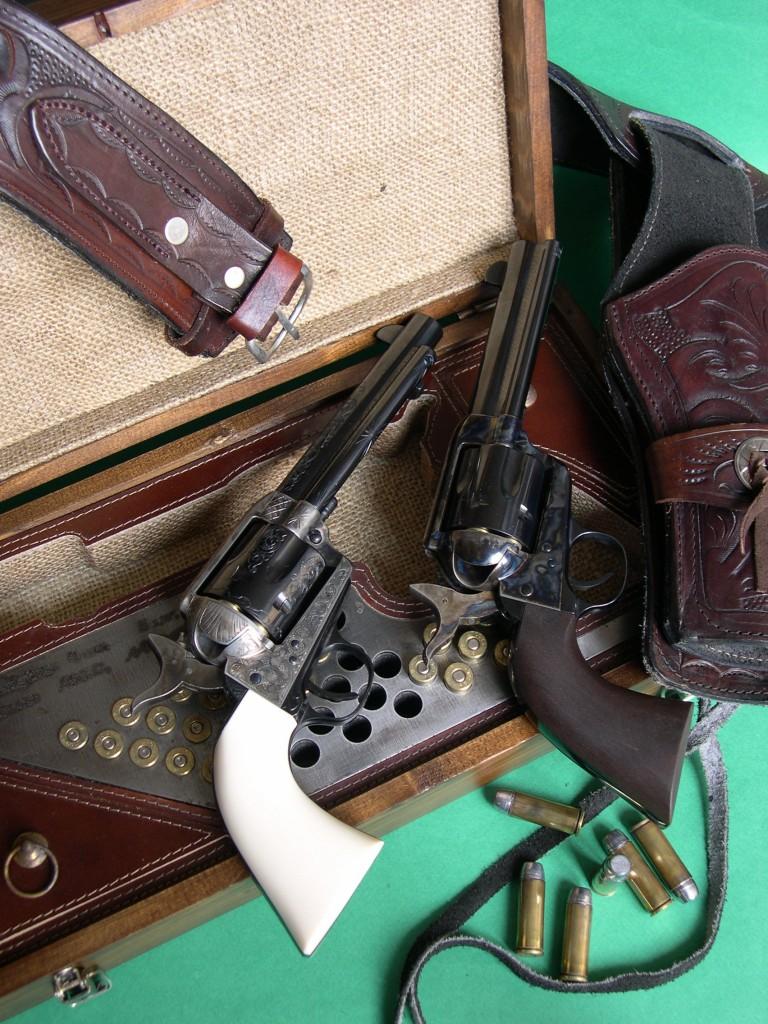 Les répliques du Colt Single Action Army 1873 « Peacemaker » produites par les firmes italiennes Pietta et Uberti sont posées sur un coffret « Old West » fabriqué par Pietta, originale reproduction d'un modèle ancien en pin, garni de toile et de cuir, et accompagnées d'un holster en cuir ciselé de fabrication mexicaine.