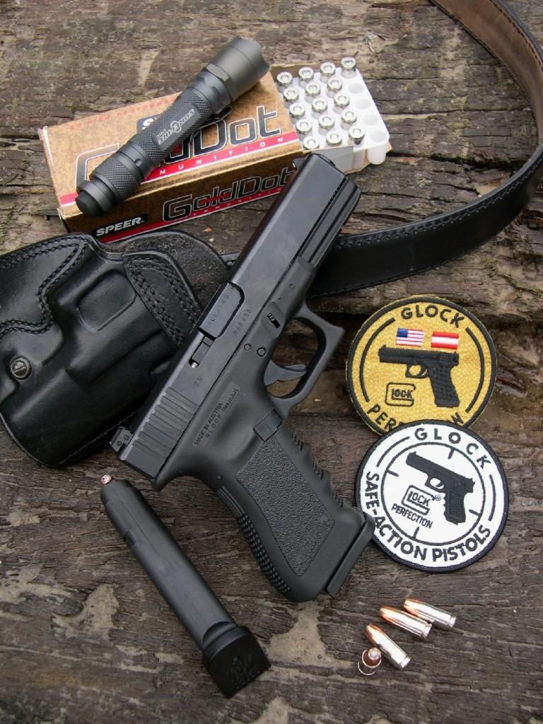 Ce Glock 17 de la troisième génération est ici accompagné d'une boîte de cartouches Speer Gold Dot, d'un holster de dos à port horizontal fabriqué Galco (USA) et d'une lampe torche SureFire A2 « Aviator » (USA).