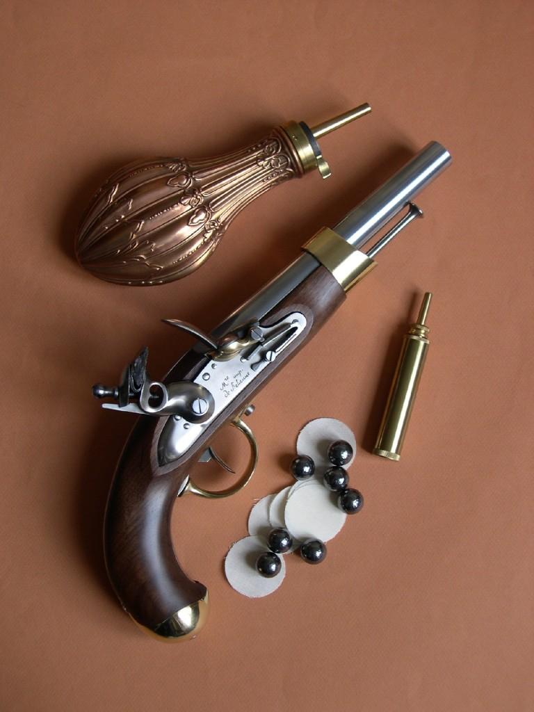 La réplique du pistolet an XIII, réalisée par le fabricant italien Davide Pedersoli, accompagnée ici de balles sphériques de calibre .675 (17,15 mm), en plomb martelé, fabriqués en Allemagne par Haendler & Natermann, de calepins « Black Powder N°1 », en pur coton pour calibre .62 à .69, fabriqués par Pedersoli, d'une poire à poudre en cuivre d'un modèle civil et d'une petite poire d'amorçage en laiton contenant le pulvérin (poudre noire fine PNF4 pour l'amorçage du bassinet).