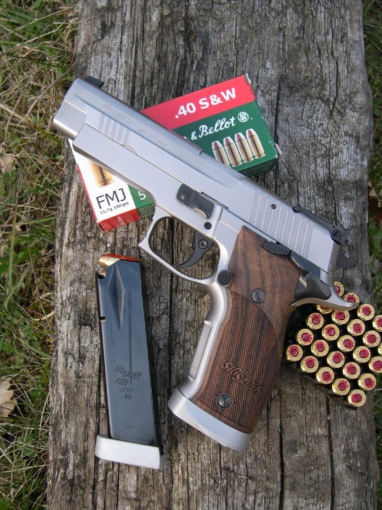 Mis au point par Sigarms en collaboration avec des tireurs sportifs de haut niveau, le modèle X-Five est considéré comme « Out of the box competition firearm », c'est-à-dire un pistolet capable de rivaliser au plus haut niveau des matches IPSC en classe standard sans nécessiter les améliorations habituellement apportées par les armuriers aux modèles de grande série. Le SIP P-226 X-Five est accompagné ici de son chargeur de rechange, d'une capacité de 12 coups en calibre .40 S&W et d'une boîte de cartouches fabriquées par la firme tchèque Sellier & Bellot.