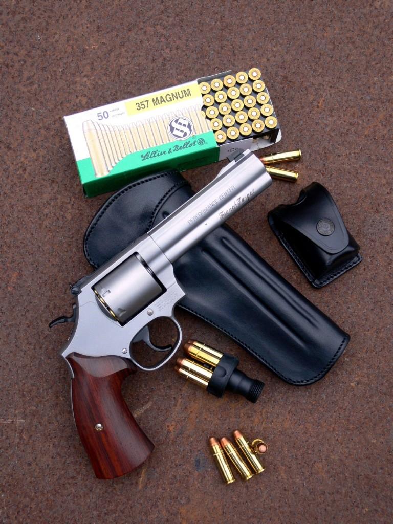 Ce Smith & Wesson modèle 686 « French Target », réalisé en série limitée, se démarque par l'aspect sobre et massif que lui confère son canon lourd, son barillet sans cannelures, sa poignée lisse et sa finition en acier inoxydable satiné. Il reçoit un canon de 5 pouces (127 mm), une longueur peu courante qui constitue un bon compromis entre la maniabilité des revolvers de défense à canon de 4 pouces et les aptitudes au tir de précision des revolvers à canon de six pouces, plus spécialement destinés au tir sportif. Il est accompagné ici d'un speed loader automatique (Variant) et d'un porte speed loader en cuir (GK).