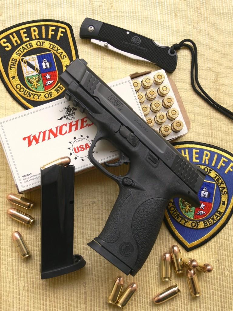 Prioritairement destiné à être employé comme arme de service, comme l'indique très clairement sa dénomination, ce modèle « Military & Police » est conçu pour être porté avec une cartouche chambrée, afin d'être constamment prêt à l'emploi. Il est ici accompagné par son chargeur de rechange d'une contenance de 10 coups, un couteau pliant ultra léger du même fabricant, une boîte de cartouches « Target/Range » à balle blindée de 230 grains manufacturée par la maison Winchester et de badges des forces de l'ordre aux Etats-Unis.