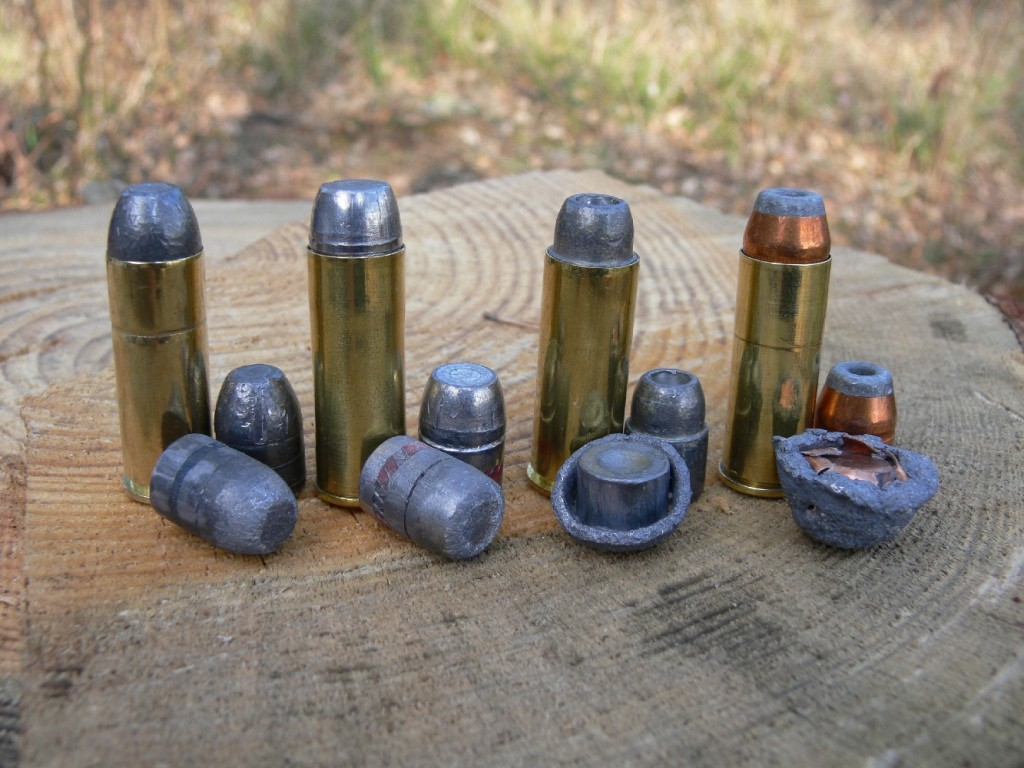 Quatre munitions de calibre .45 Long Colt, accompagnées d'un projectile tiré dans le sable, de gauche à droite : Magtech Cowboy Action à balle en plomb de 250 grains (199 m/s) ; balle Samson semi-wadcutter en plomb de 255 grains rechargée avec 0,40 g de Ba10 (250 m/s) ; Federal Classic à balle en plomb semi-wadcutter expansive de 225 grains (241 m/s) ; balle Sierra Power Jacket demi-blindée expansive de 240 grains rechargée avec 0,70 g de N340 (306 m/s).