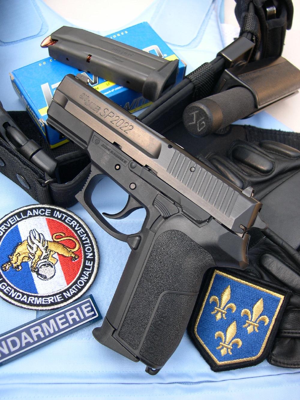 Le SIG-Sauer SP-2022, accompagné de cartouches Speer Lawman et d'accessoires utilisés par les gendarmes du PSIG (Peloton de Surveillance et d'Intervention de la Gendarmerie) : ceinturon portant l'étui, les menottes et une matraque télescopique, gants renforcés et insignes de reconnaissance.
