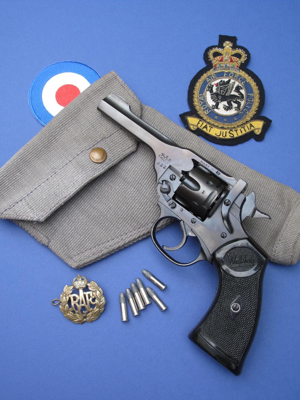 Le revolver Webley Mark IV « RAF 22 Special », entouré de quelques accessoires d'époque : un insigne de casquette en métal de la RAF, un holster en web de la RAF (couleur gris bleu) pour Webley ou Enfield de calibre .38 daté de 1943 et un patch en tissu brodé de la RAFP (Royal Air Force Police).
