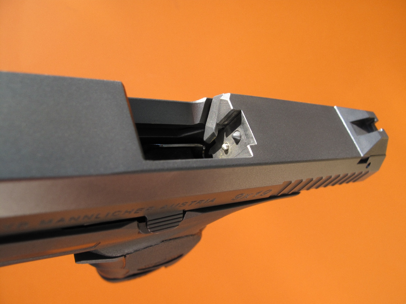 L'extracteur du Steyr, qui peut être comparé à celui d'une carabine à culasse de type Mauser, bénéficie d'une efficacité et d'une robustesse incomparables, en contrepartie d'un petit inconvénient : toute cartouche doit obligatoirement transiter par le chargeur pour pouvoir être chambrée. Cette vue permet d'observer, au-dessus du percuteur, le palpeur de l'indicateur de chargement.