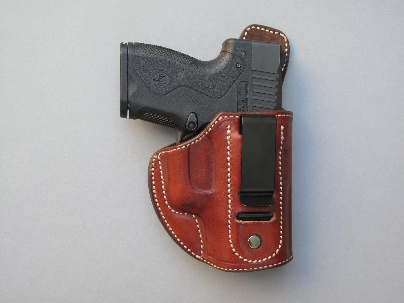 """Pistolet Beretta """"Nano"""", glissé dans un holster en cuir de type """"Inside"""", muni d'un clip, d'un renfort interne de carcasse en acier inoxydable et doublé intérieurement en croûte velours (La Sellerie du Thymerais)."""