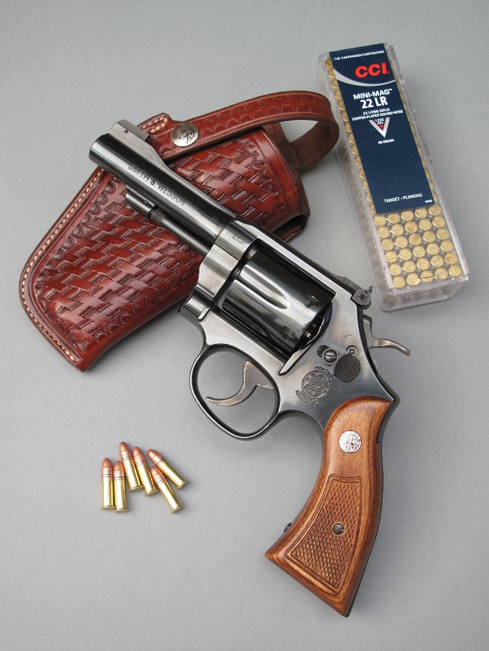Le Smith & Wesson modèle 18 « Combat Masterpiece », un revolver tout acier de conception traditionnelle, est accompagné ici par une boîte de 100 cartouches de calibre .22 Long Rifle à haute vitesse et par un étui de ceinture en cuir finition basket, réalisé par la maison française La Sellerie du Thymerais, qui reprend l'esprit d'époque des holsters conçus dans les années 1920 par le sheriff et gunfighter Tom Threepersons (1889-1969) et réalisés à El Paso, au Texas, par le sellier Samuel Dale Myres (1871-1953).