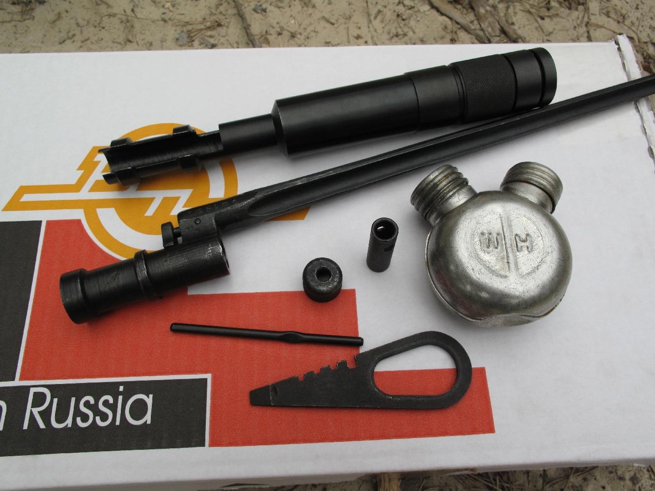 Quelques accessoires pour le fusil Mosin-Nagant, de bas en haut : - outil tournevis, permettant également de dévisser le percuteur et de contrôler sa longueur ; - embout avec son axe transversal servant de poignée à la baguette de nettoyage ; - protège-bouche, pour éviter le frottement de la baguette de nettoyage ; - huilier en aluminium à 2 compartiments étanches (produit nettoyant et lubrifiant) : - baïonnette, dont l'extrémité peut également être utilisée comme tournevis ; - modérateur de son à membranes en caoutchouc et fixation à baïonnette (chez AAS Sniper).