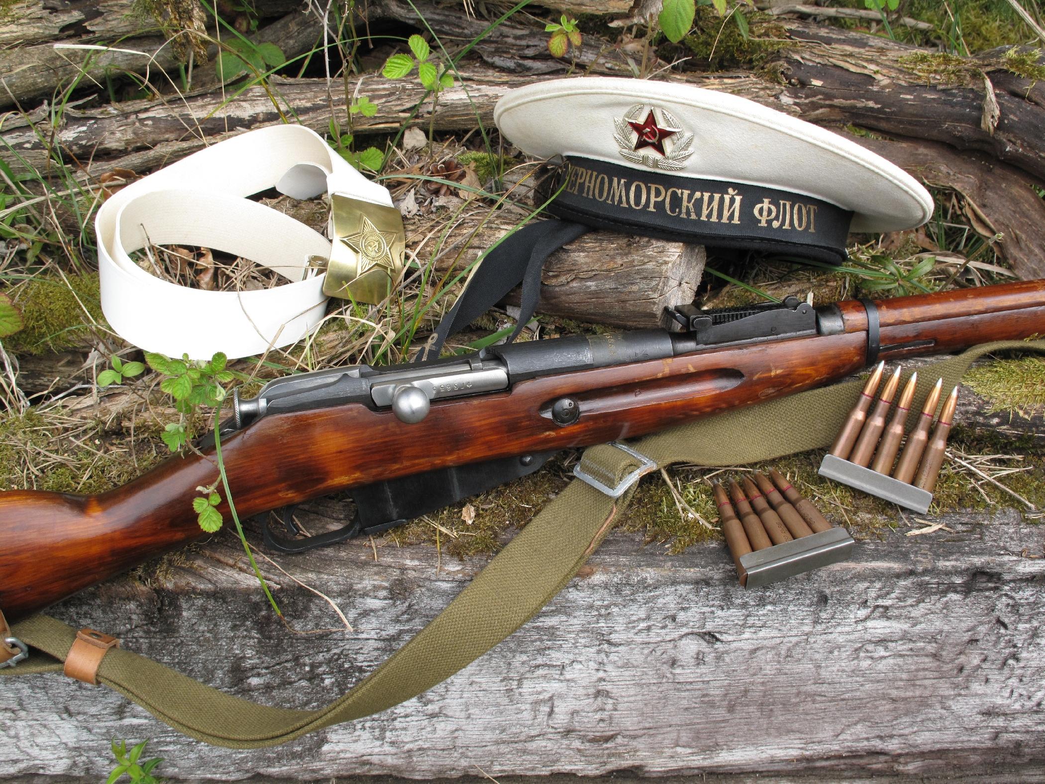 Le Mosin-Nagant modèle 1891/30 de notre test est équipé ici de sa bretelle en toile et cuir. Il est accompagné par deux clips de cinq cartouches de calibre 7,62 x 54 R provenant des surplus militaires soviétiques, un bachi et un ceinturon de la marine soviétique.