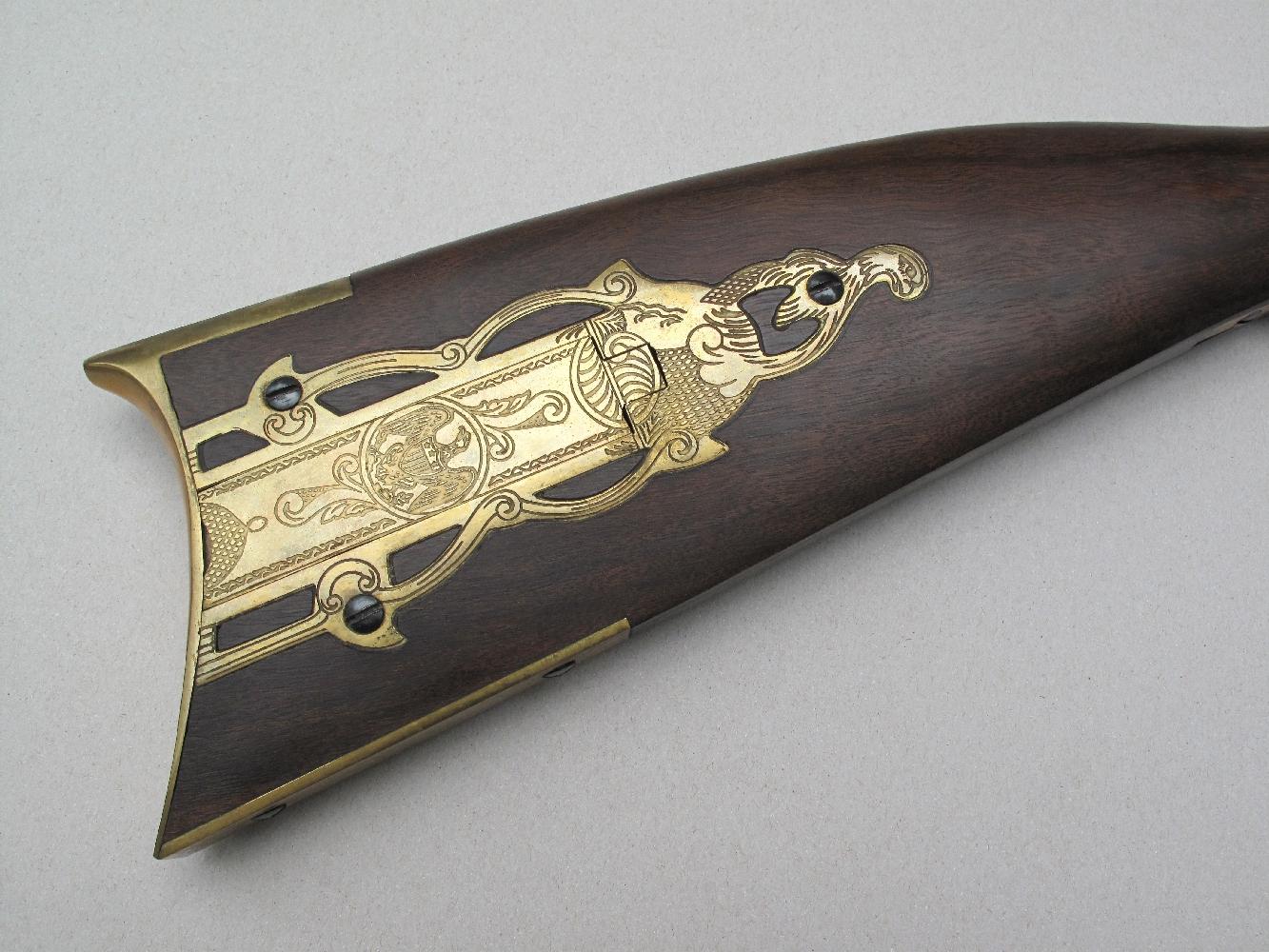 La crosse, en noyer moiré, est décorée d'un superbe « Patchbox » (boîte à calepins) en laiton, muni d'un couvercle à charnière et gravé de motifs décoratifs comprenant l'aigle américain.
