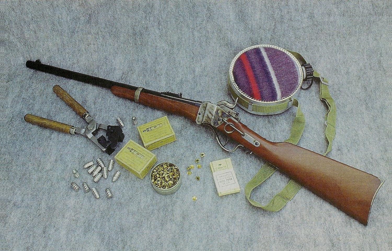 La réplique Pedersoli de la carabine de cavalerie Sharps modèle 1863 est accompagnée ici de son moule à balles, de projectilés coulés, d'amorces à ailettes de type militaire, de papier nitraté et de deux boîtes de cartouches combustibles.