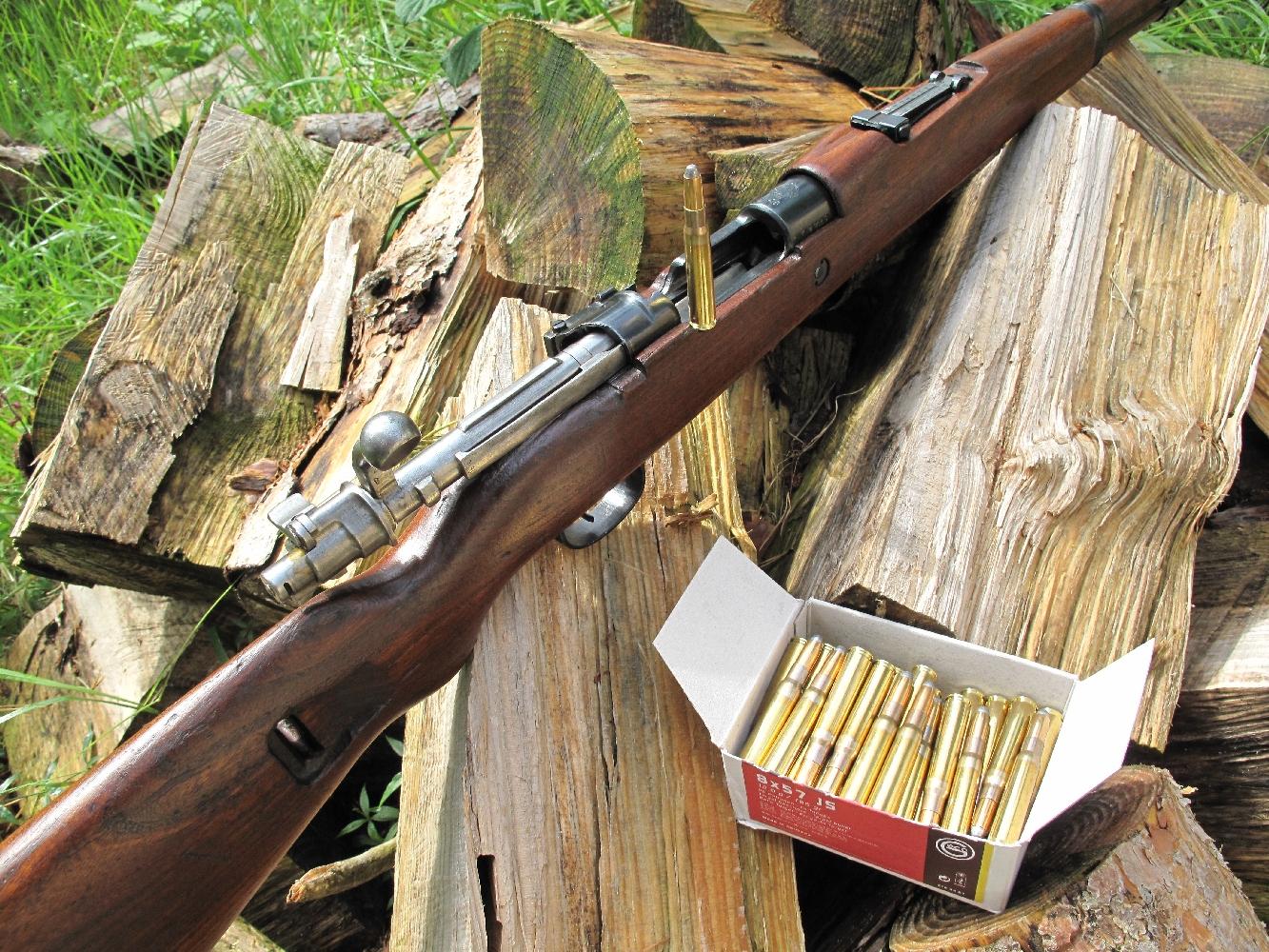 Le fusil M48, dont on remarque ici, la culasse étant ouverte, le levier d'armement dont la boule est partiellement rognée afin de ne pas nécessiter un évidement du bois de la monture, est accompagné de cartouches de calibre 8 x 57 JS manufacturées par la firme allemande Geco.