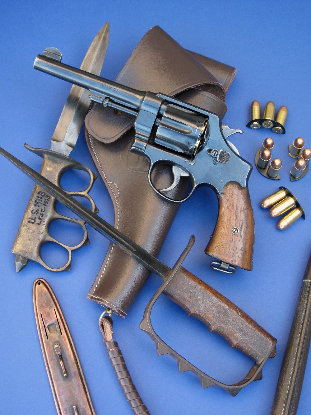 Le revolver S&W modèle 1917 que nous avons testé est accompagné ici de son holster en cuir (copie), de clips chargeurs en demi-lune (copies) garnis de cartouches modernes de calibre .45 ACP et des poignards de tranchée américains modèles 1917 et 1918 (authentiques), prêtés par la maison AAS (www.aassniper98.com).