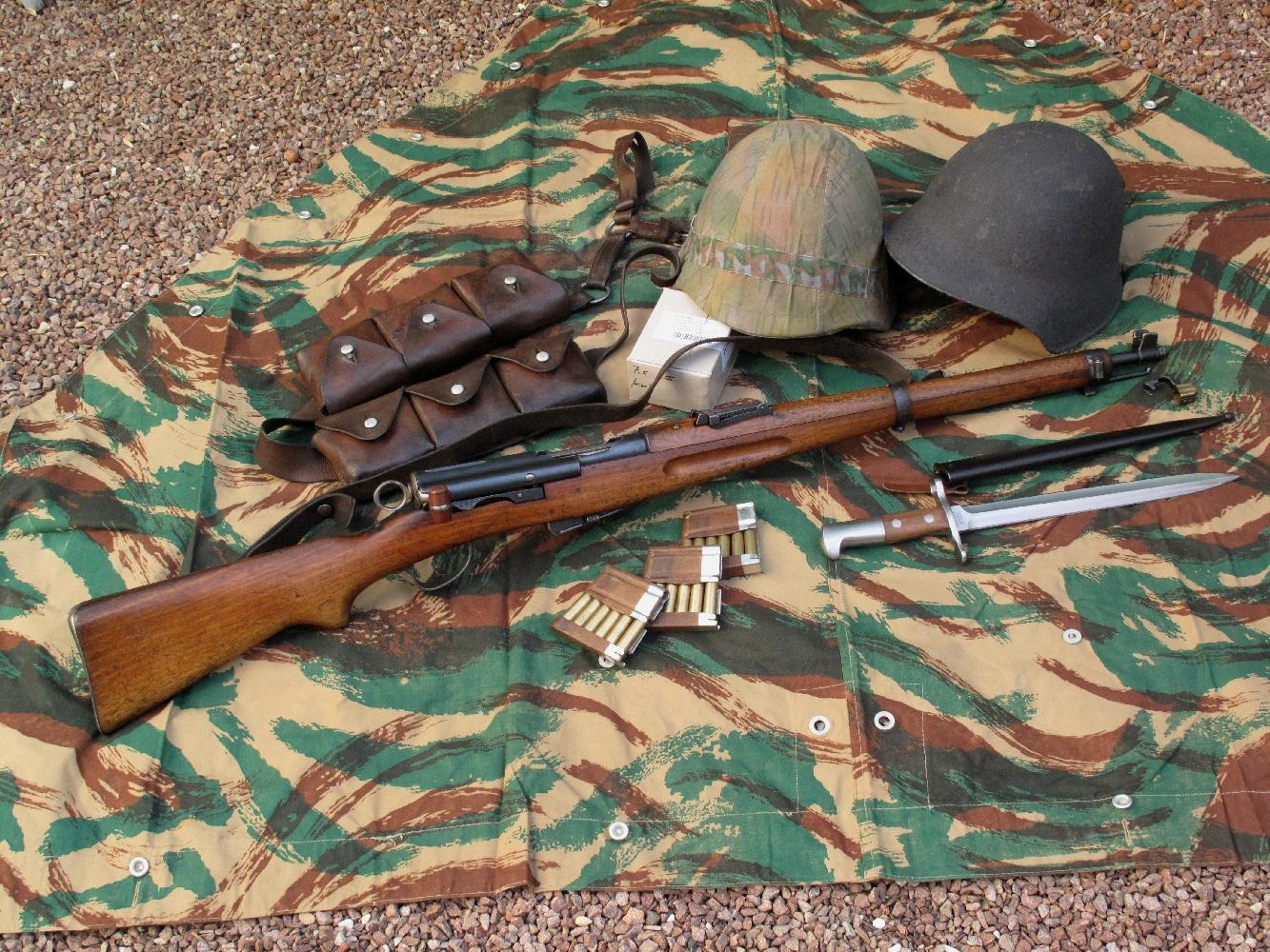 Le mousqueton suisse K11 employé pour notre banc d'essai est accompagné ici par divers accessoires aimablement prêtés par la société AAS (www.aassniper98.com) : deux casques suisses modèle 1918 (dont l'un est muni de son couvre-casque amovible) ; une baïonnette suisse modèle 1918-31 ; une cartouchière suisse en cuir dont chacune des six poches peut recevoir deux lames-chargeurs et un bouchon de canon.