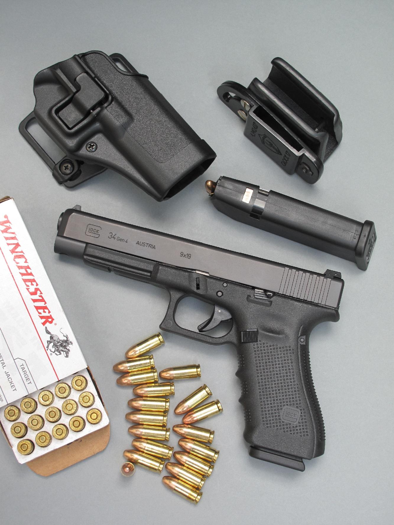 Le pistolet G34 Gen4 est accompagné ici par un holster actif CQC Serpa Concealment de la firme Blackhawk et un porte-chargeur de la marque Safariland. Le holster, moulé en polymère, dispose d'un système de rétention à mise en œuvre automatique dont le déverrouillage est obtenu au moyen d'un bouton-poussoir idéalement placé au niveau de l'index qui saisit l'arme. Le porte-chargeur, en polymère recouvert de cuir, dispose de réglages assurés par des vis au niveau de la rétention et de l'inclinaison.