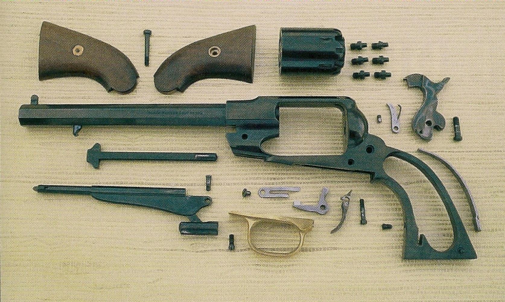 Vue de l'ensemble des pièces qui composent l'arme après avoir terminé le grand démontage. Le démontage des pièces ne doit pas être poussé plus avant. Certaines sont soudées (guidon sur le canon), d'autres fermement bloquées et parfois collées (canon sur la carcasse), d'autres encore serties ou matées (petit ressort à lame sur le doigt élévateur).