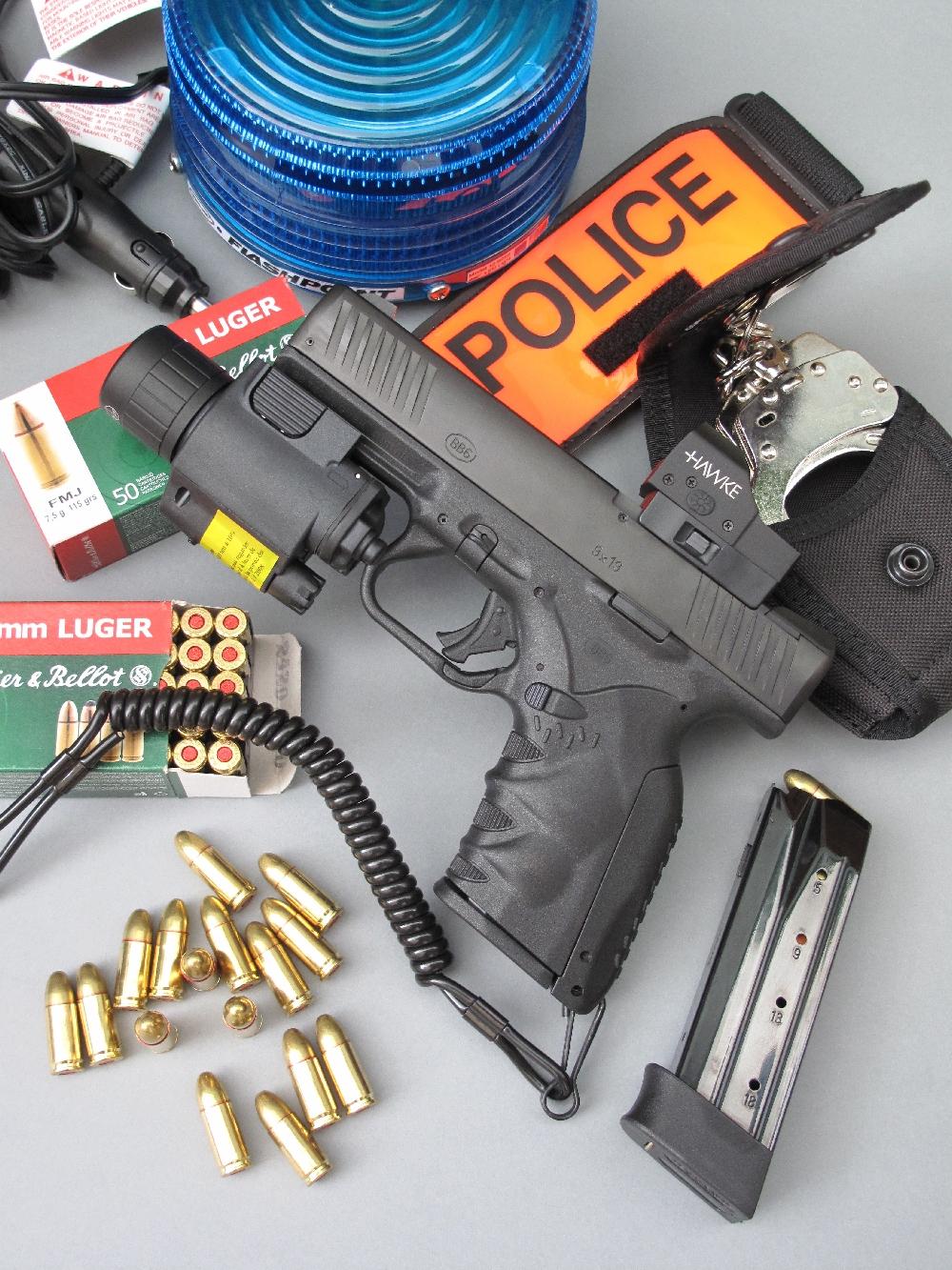 Le pistolet semi-automatique BB6 est équipé ici d'un viseur point rouge reflex de la marque américaine Hawke et d'un ensemble RTI Optics regroupant une lampe torche et un pointeur laser. Les accessoires en Cordura, brassard et porte-menottes, sont issus de la maison française GK Professional, tandis que le gyrophare « Flash Point » est estampillé SHO-ME, une marque commerciale de la firme américaine Able 2 Products, basée dans la Missouri.