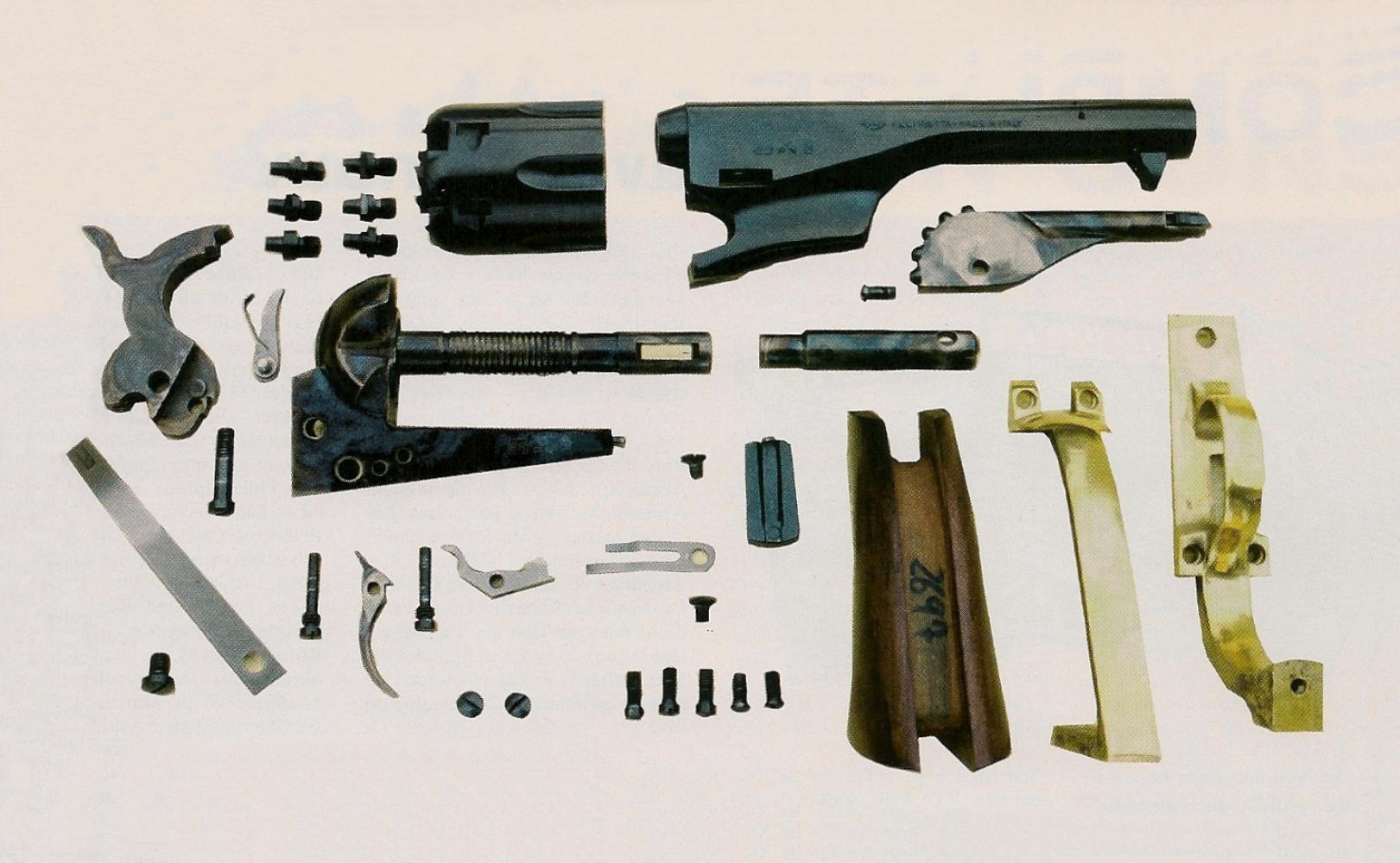 Vue d'ensemble des pièces qui composent cette réplique de Colt modèle 1861 Navy. Pousser plus avant le démontage est fortement déconseillé : vous ne devez pas tenter de séparer l'axe du barillet du bâti sur lequel il est vissé, ni le petit ressort à lame du doigt élévateur sur lequel il est serti.