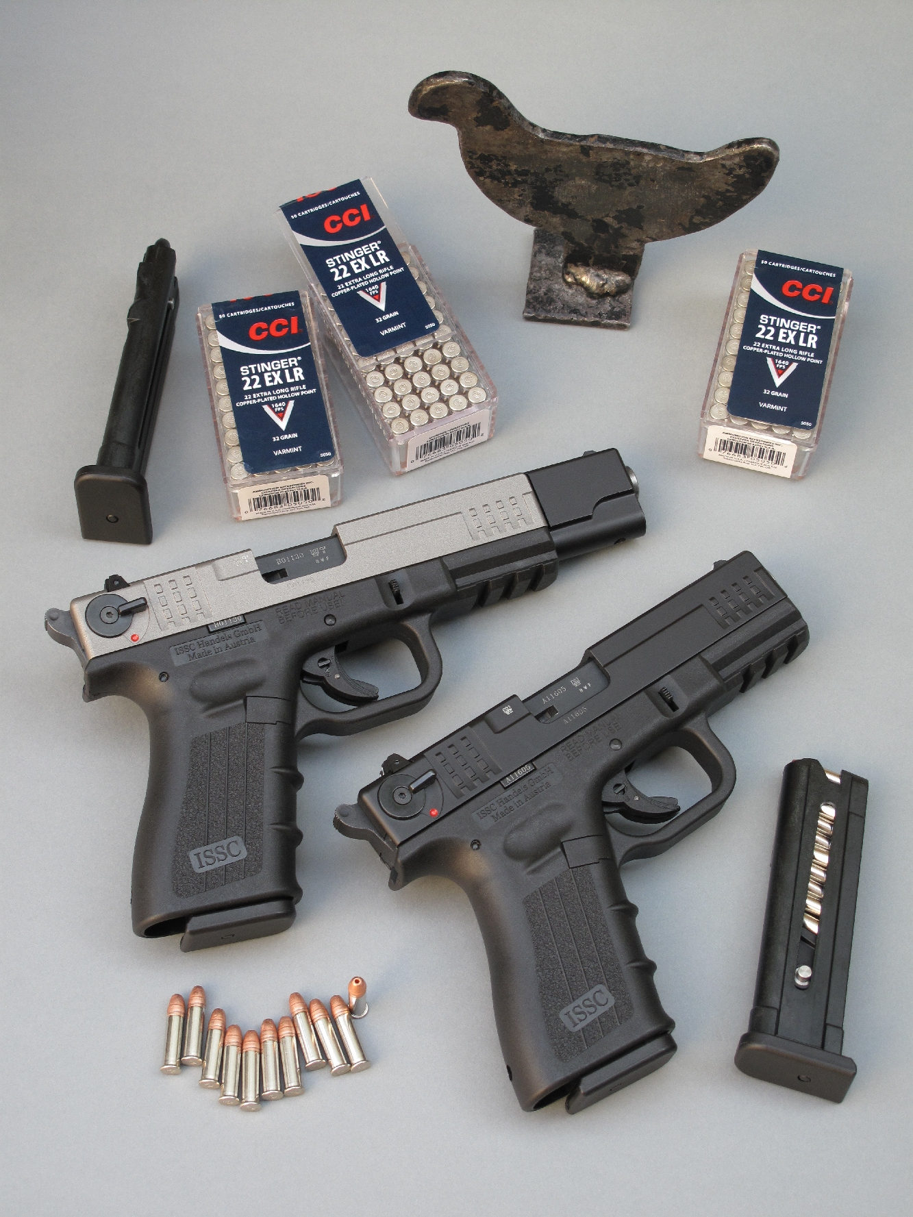 Les pistolets ISSC M22 modèles Standard et Target sont accompagnés ici par leur chargeur de secours, quelques boîtes de munitions CCI « Stinger » de calibre .22 Long Rifle à très haute vitesse et une mini-silhouette métallique en acier.