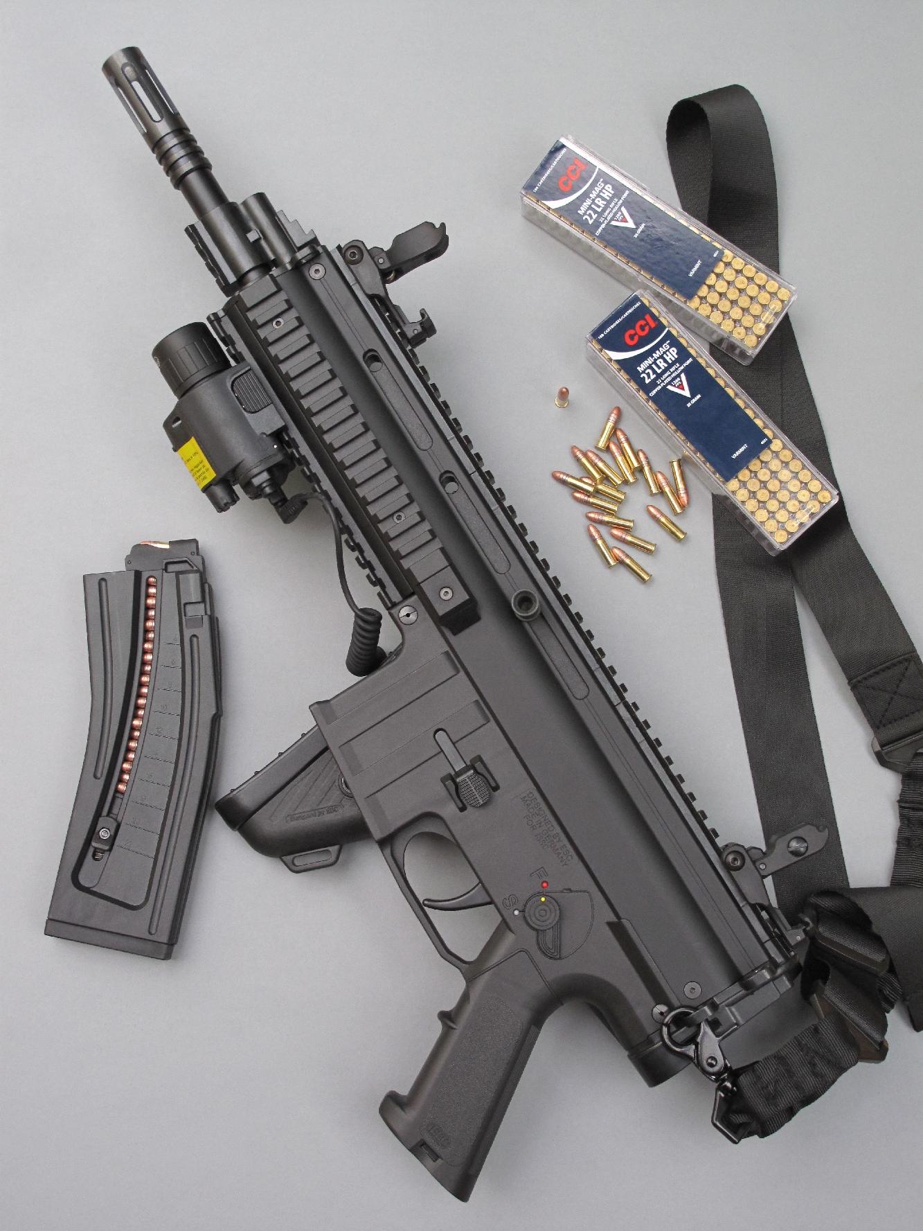 La carabine ISSC modèle MK22 Commando est équipée ici d'une bretelle à point d'accrochage unique et d'un accessoire tactique combiné RTI Optics regroupant lampe torche et désignateur laser. Elle est accompagnée par son chargeur de 22 coups et par deux boîtes de munitions de calibre .22 Long Rifle CCI Mini-Mag.