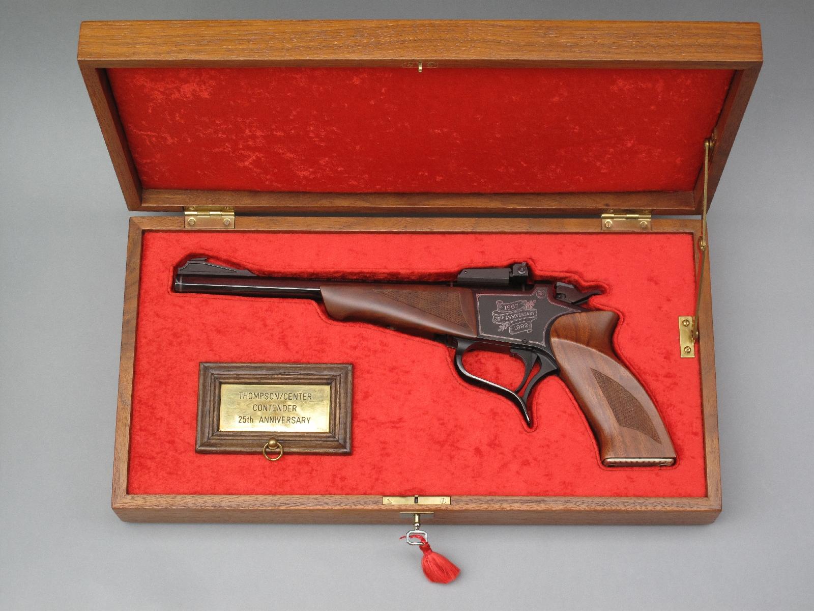 Ce coffret en noyer, agencé « à la française » et garni de velours rouge, a été réalisé pour un pistolet Contender en calibre .22 Long Rifle commémoratif du 25ème anniversaire (1967-1992) de la firme américaine Thompson/Center.