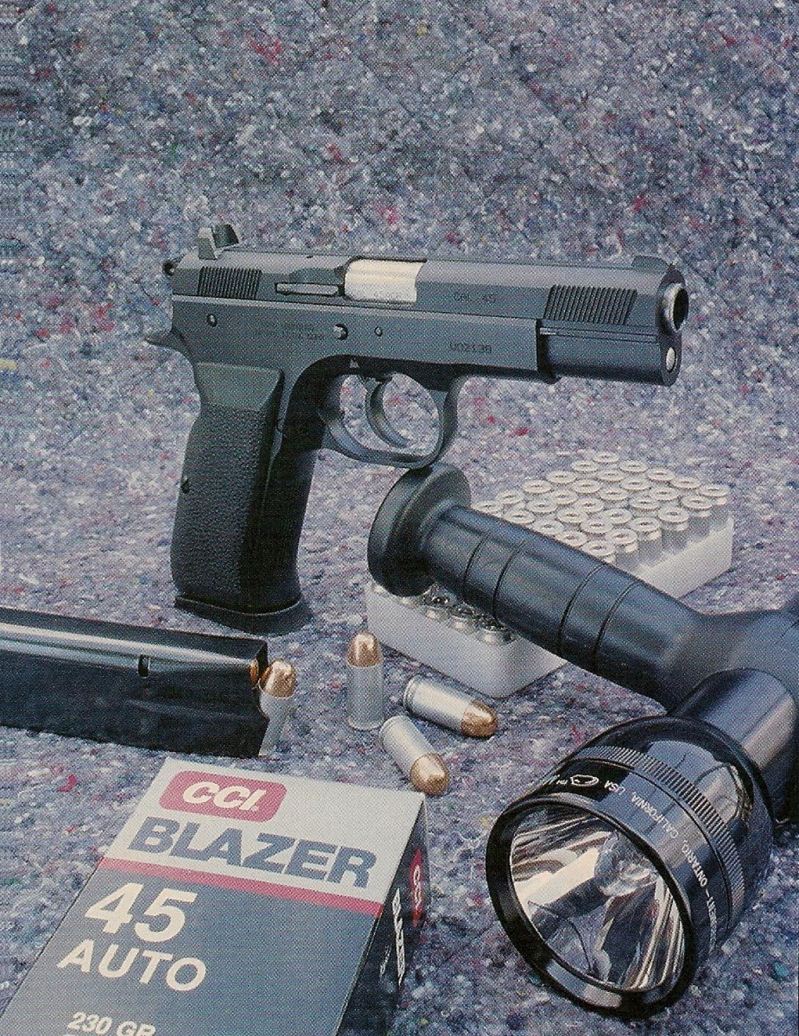 Le pistolet Tanfoglio P-45 accompagné de munitions CCI Blazer à douille jetable calibre .45 ACP et d'une lampe-torche Mag-lite avec poignée REF III.