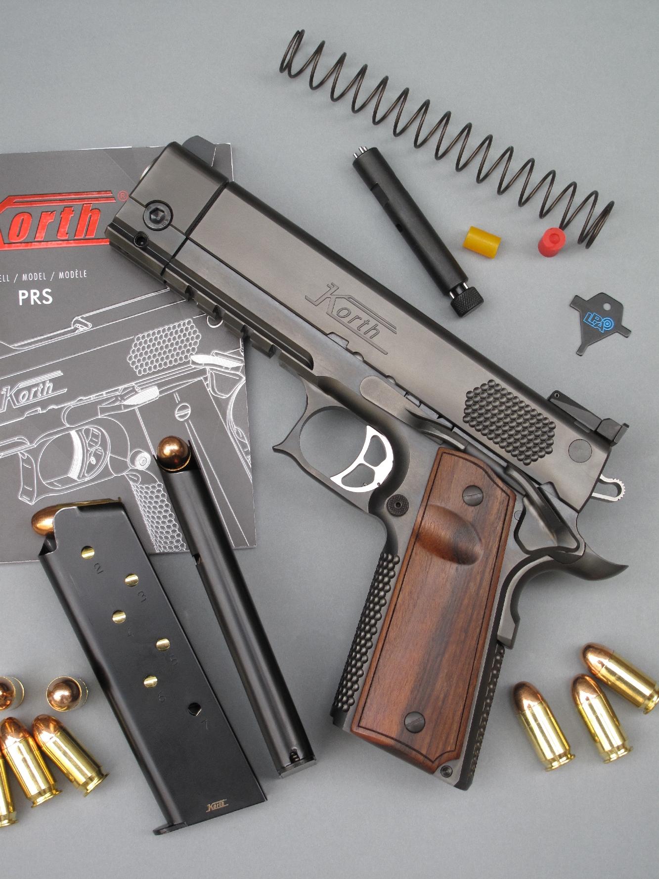 Le pistolet Korth PRS 5 pouces est accompagné ici par les divers éléments fournis avec l'arme par le fabricant, à savoir : deux chargeurs de 7 coups ; deux ressorts récupérateurs (le modèle le plus puissant étant installé sur l'arme) ; trois amortisseurs de glissière (le modèle le plus souple étant installé sur l'arme) ; un outil spécifique pour le démontage ; une clé multiple pour le réglage de la hausse et un manuel utilisateur.