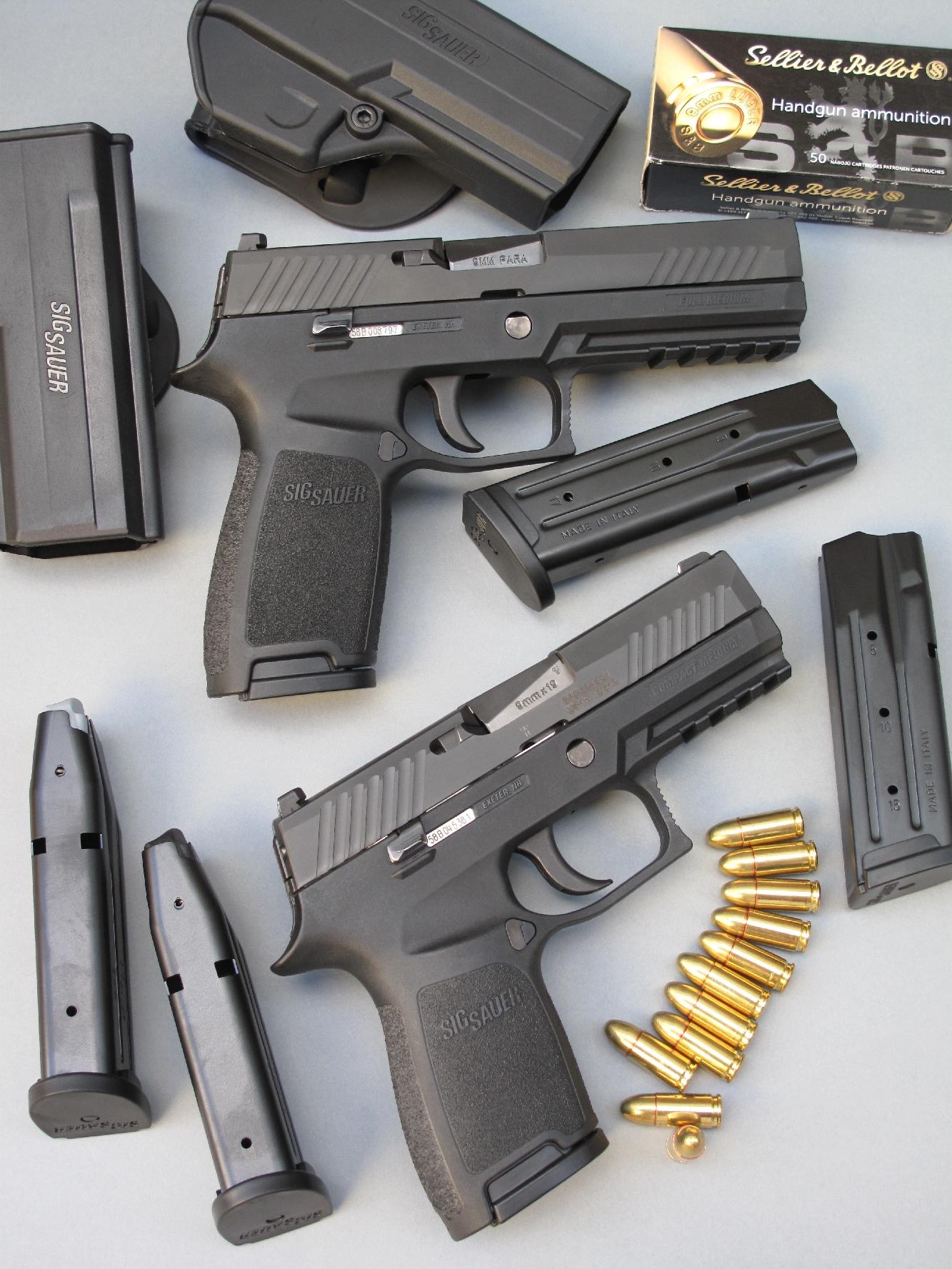 Les deux pistolets SIG-Sauer p-320, Compact et Full size, sont accompagnés ici par leurs chargeurs et holsters respectifs, chaque arme étant livrée avec trois chargeurs et un holster de ceinture de type « Paddle », moulé en polymère.