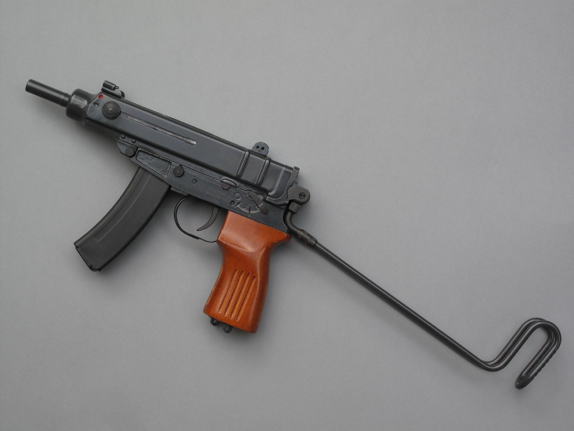 Sa trop courte et très rustique crosse squelette en fil de fer, qui se rabat sur le dessus de l'arme sans entraver la prise de visée, n'en remplit pas moins sa fonction qui est d'offrir une précision supérieure à celle d'un pistolet lorsque cela s'avère nécessaire.