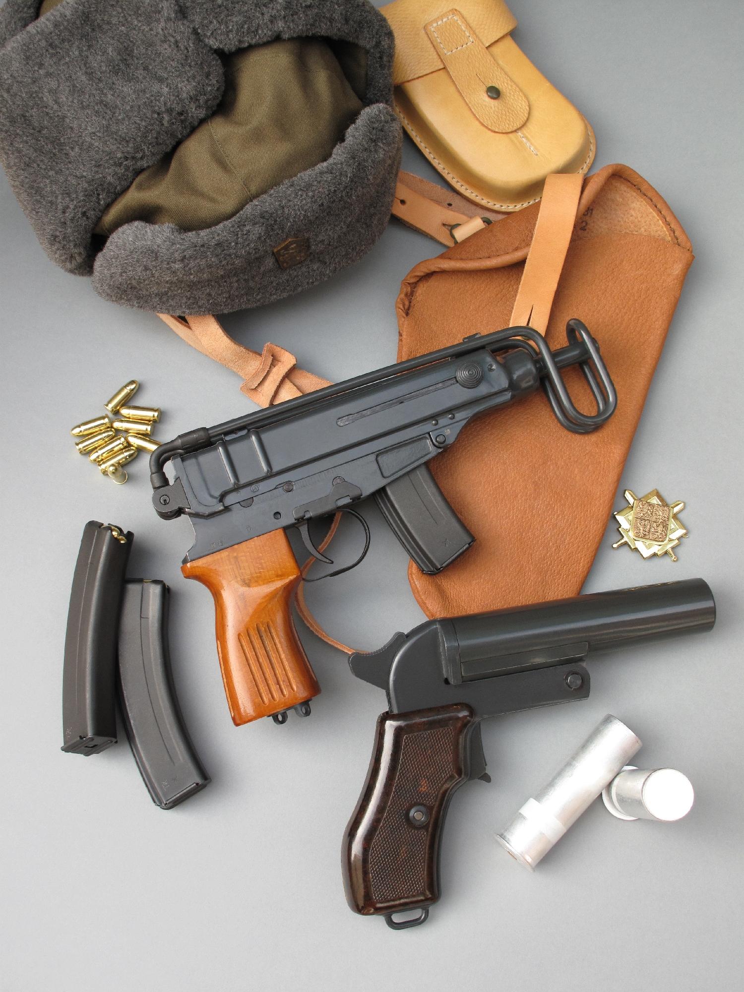 Le pistolet CZ Skorpion Vz.61 est accompagné ici par un holster d'épaule en cuir (daté de 1981), un porte-chargeurs en cuir, deux chargeurs de vingt coups, une chapka de l'armée tchécoslovaque, un insigne de casquette d'officier et un pistolet lance-fusées tchèque Vz.44/81 (daté de 1982, copié sur le modèle russe SPSh 1944) accompagné par deux fusées éclairantes de calibre 4 (26,5 mm).