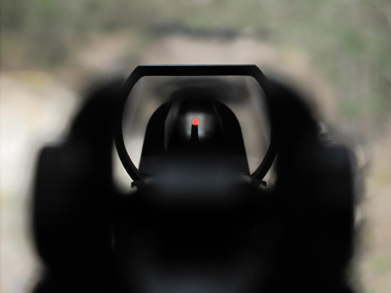 Cette photo prise en plaçant l'objectif à la place de l'œil du tireur, tout près de l'œilleton de la hausse (lequel apparaît ici flou en raison de la profondeur de champ réduite) permet d'observer la concordance entre les deux systèmes de visée, le point lumineux du viseur reflex se trouvant situé à l'extrémité supérieure du guidon.