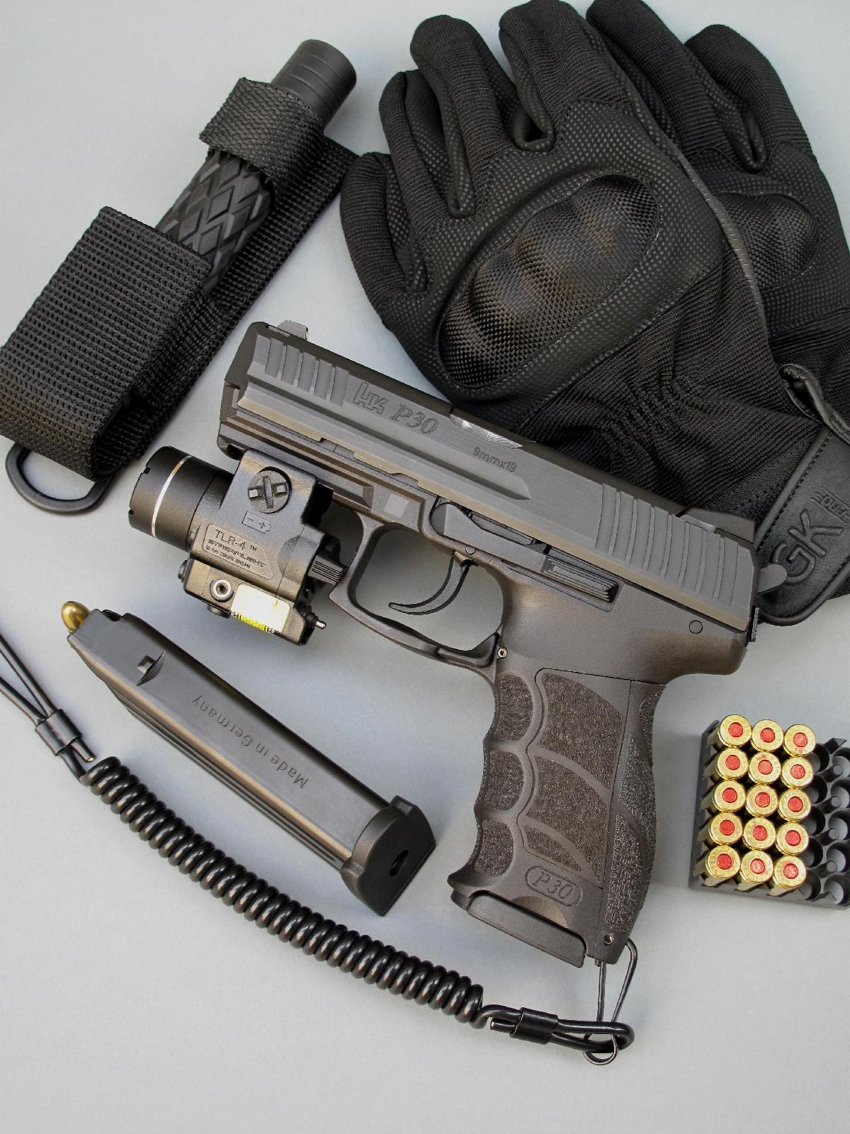 Le pistolet HK P30 est muni ici d'un ensemble compact Streamlight TLR-4 combinant lampe torche et désignateur laser et il est accompagné par son chargeur de rechange, un bâton télescopique en acier trempé 16 pouces « Piranha » à poignée gainée latex et une paire de gants tactiques coqués « Blake » de la firme GK Professional.
