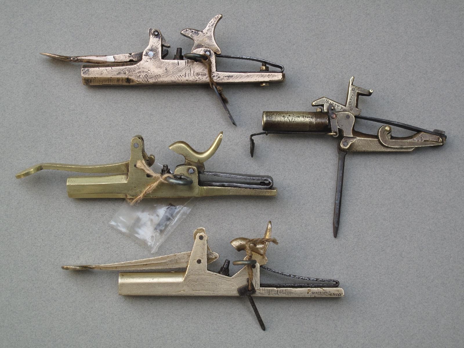 Petite collection de pistolets à taupes en bronze, de calibre 8 et 10 mm. Celui qui figure à droite se démarque par son marquage « ISABEY F. Breveté » et par le fait que son mécanisme intègre toutes les commandes nécessaires pour l'actionner, contrairement aux autres modèles qui disposent d'une goupille de sûreté et d'une barrette de déclenchement séparées.