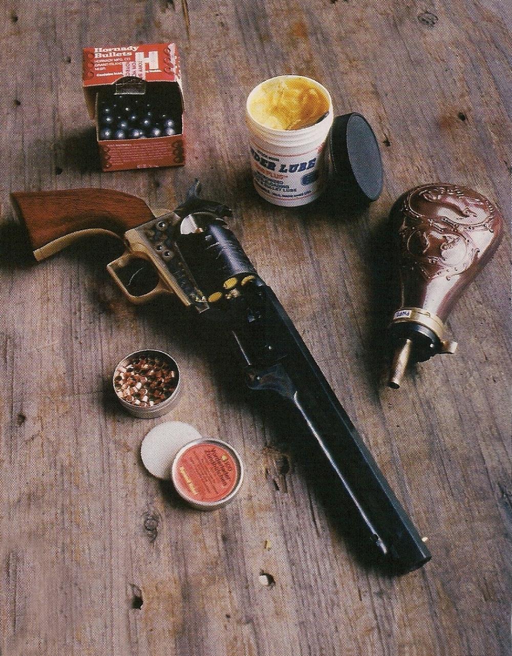 La réplique du Colt modèle 1851 Navy « Squareback », qui vient d'être chargée, est accompagnée des ingrédients indispensables à son utilisation au stand : poudre, balles, graisse et amorces.