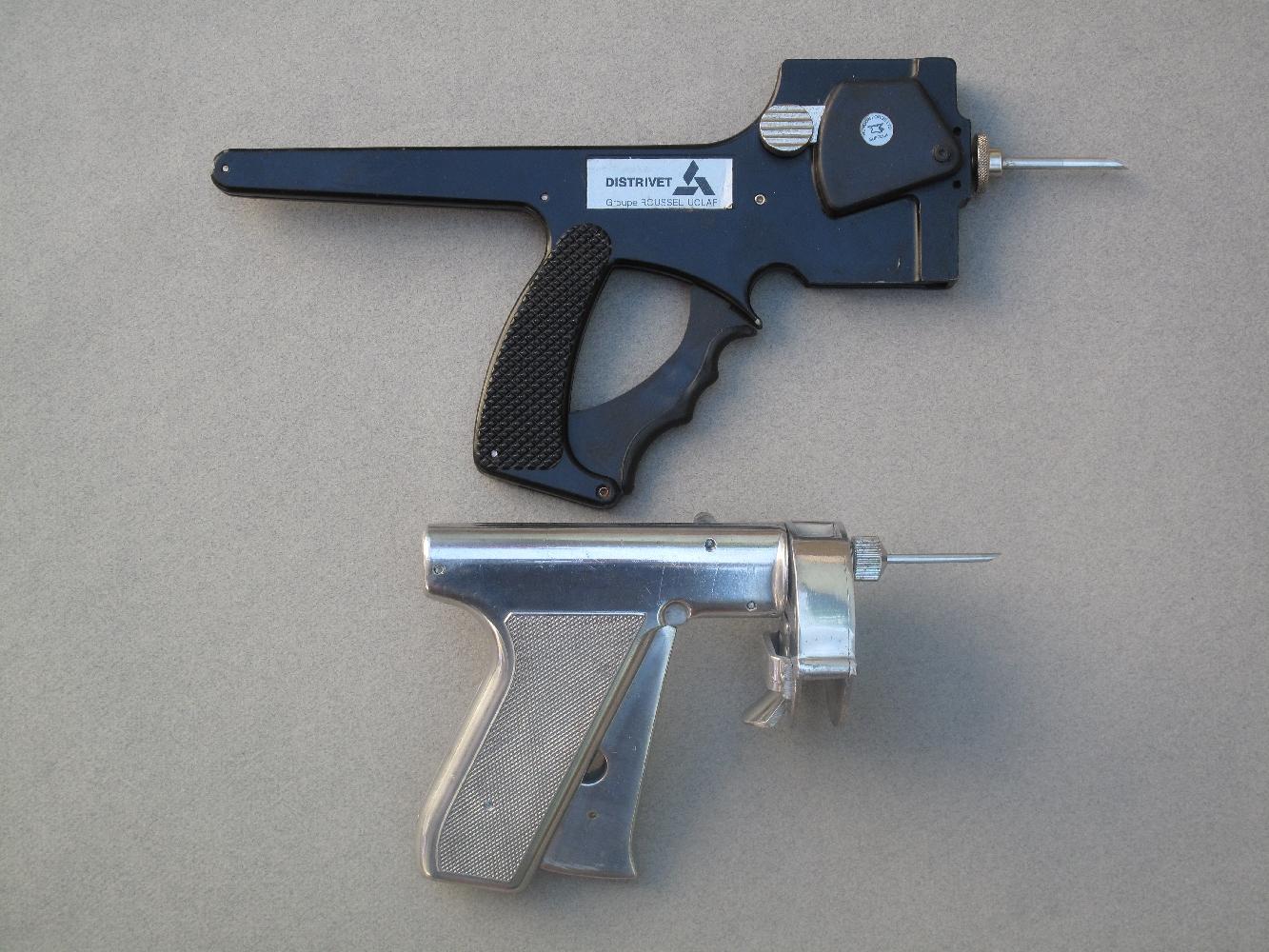 Voici deux anciens pistolets utilisés pour injecter des anabolisants (hormones de croissance) aux bovins. Celui du haut est un pistolet Distrivet, qui utilise un chargeur vertical de dix doses tandis que l'autre est un revolver RalOgun, qui se charge au moyen d'un barillet contenant vingt-quatre doses de produit.