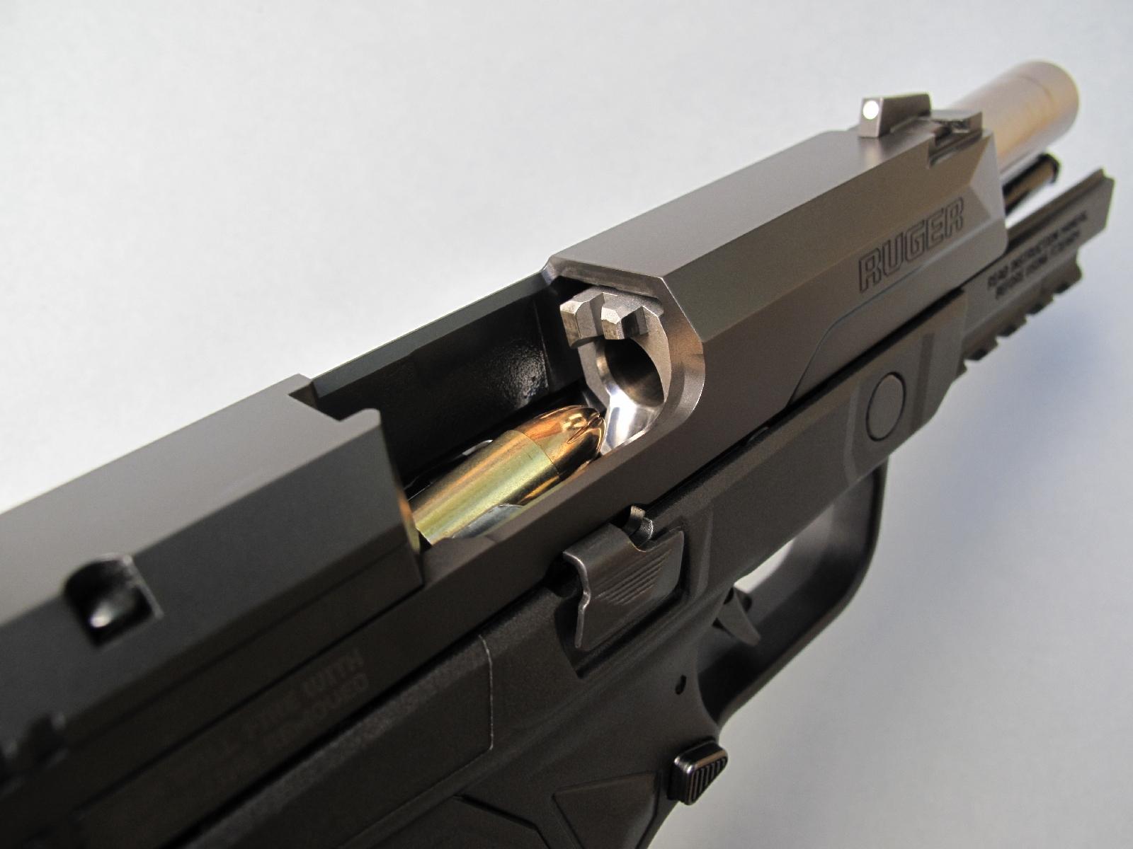 Cette vue permet d'observer, au travers de la fenêtre d'éjection, l'entrée de chambre du canon, sa courte rampe d'alimentation et la cartouche prête à être chambrée.