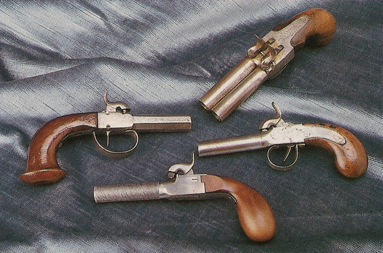 La réplique italienne est accompagnée ici par trois pistolets de poche anciens authentiques. Ces petits pistolets à coffre connurent un grand succès, comme arme de défense, de 1820 à 1860 environ, avant de céder progressivement leur place aux revolvers.