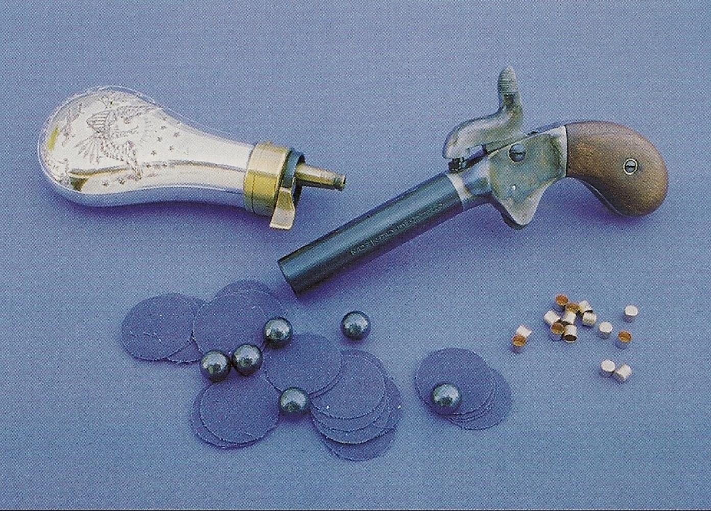 Le derringer Abilene, accompagné des accessoires nécessaires à son chargement : balles sphériques en plomb, calepins, amorces et poire à poudre.