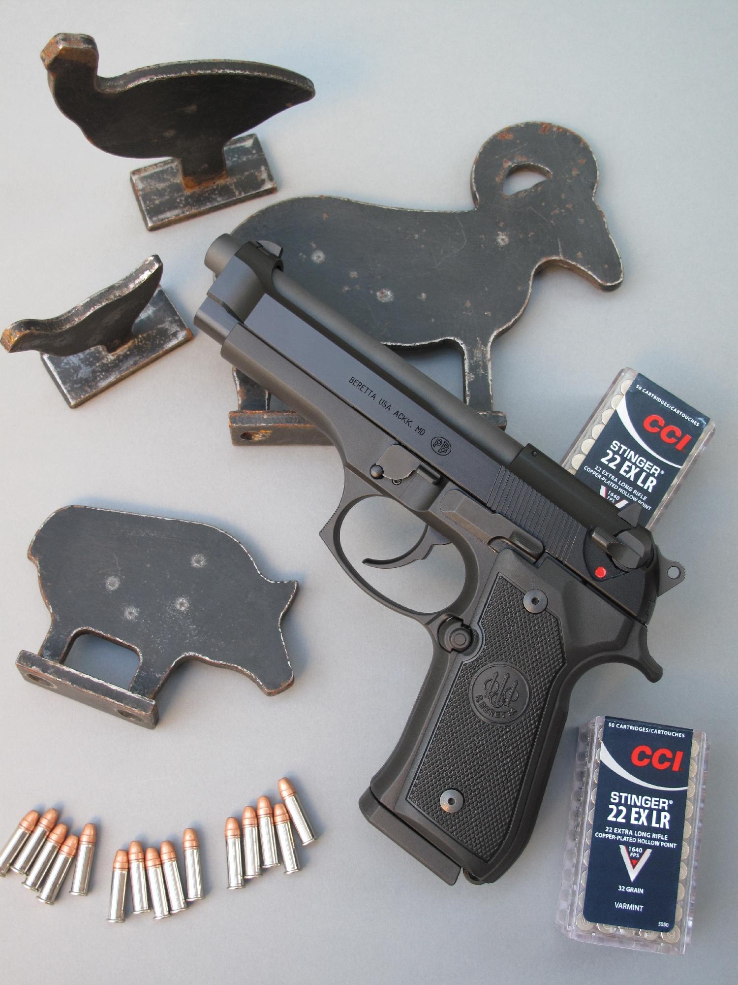 Pour les besoins de la photo, le Beretta 92 FS-22 est accompagné par les mini-silhouettes métalliques à l'échelle 1/5 dédiées aux carabines de petit calibre, lesquelles sont nettement plus petites que celles à l'échelle 3/8 normalement utilisées avec les armes de poing de calibre .22 Long Rifle.