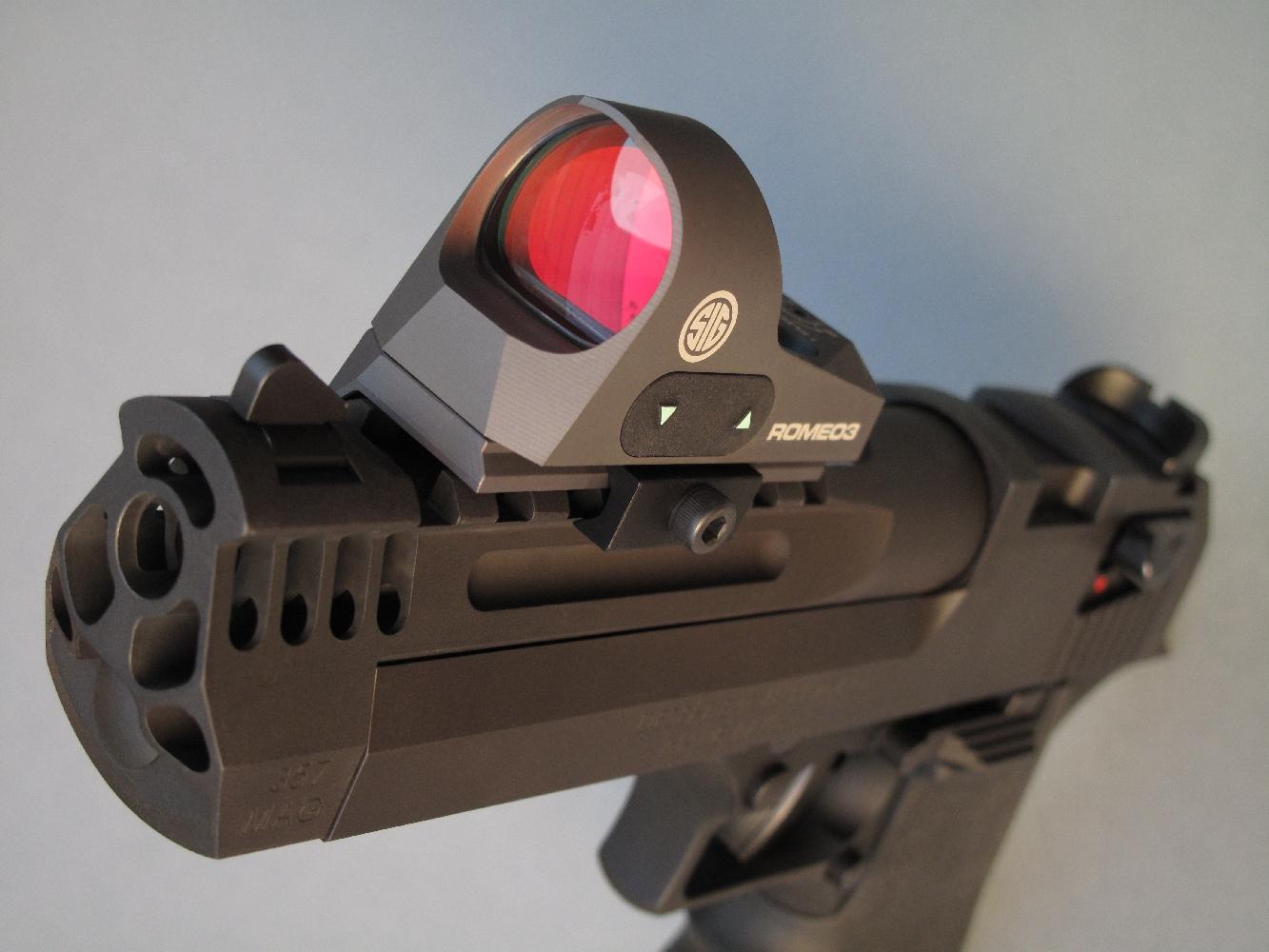 Le robuste rail Picatinny directement usiné dans la masse d'acier de son canon permet d'équiper cette arme d'une lunette grossissante ou d'un viseur à point lumineux, à l'image du modèle refex « Romeo3 » de la firme Sig-Sauer, installé ici grâce à son montage bas.