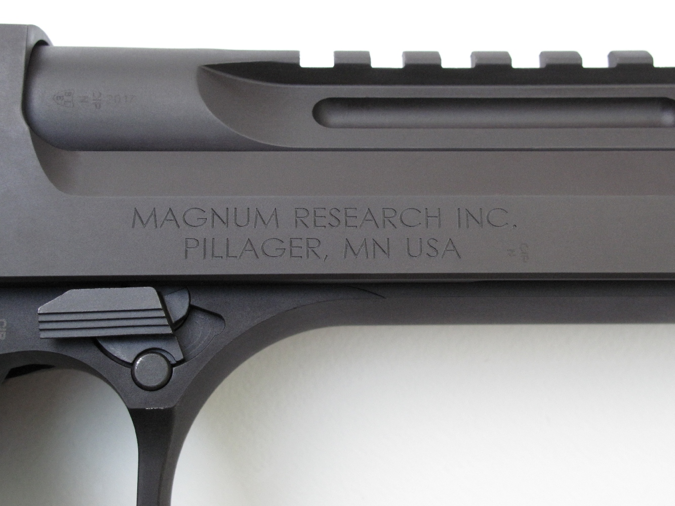 Le nom et l'adresse de la firme américaine Magnum Research, qui est à la fois concepteur et fabricant du pistolet Desert Eagle, sont gravés sur le côté droit de la glissière.