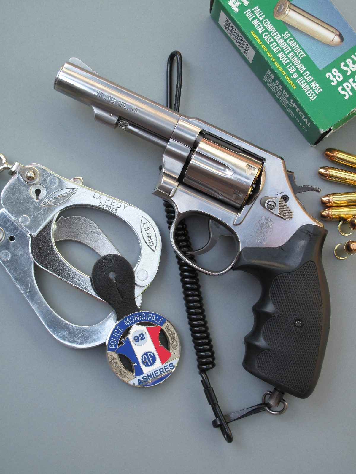 Le revolver Smith & Wesson modèle 64 est accompagné ici d'une paire de menottes, d'un badge de la police municipale et d'une boîte de cartouches de calibre .38 Special manufacturées par la firme italienne Fiocchi.
