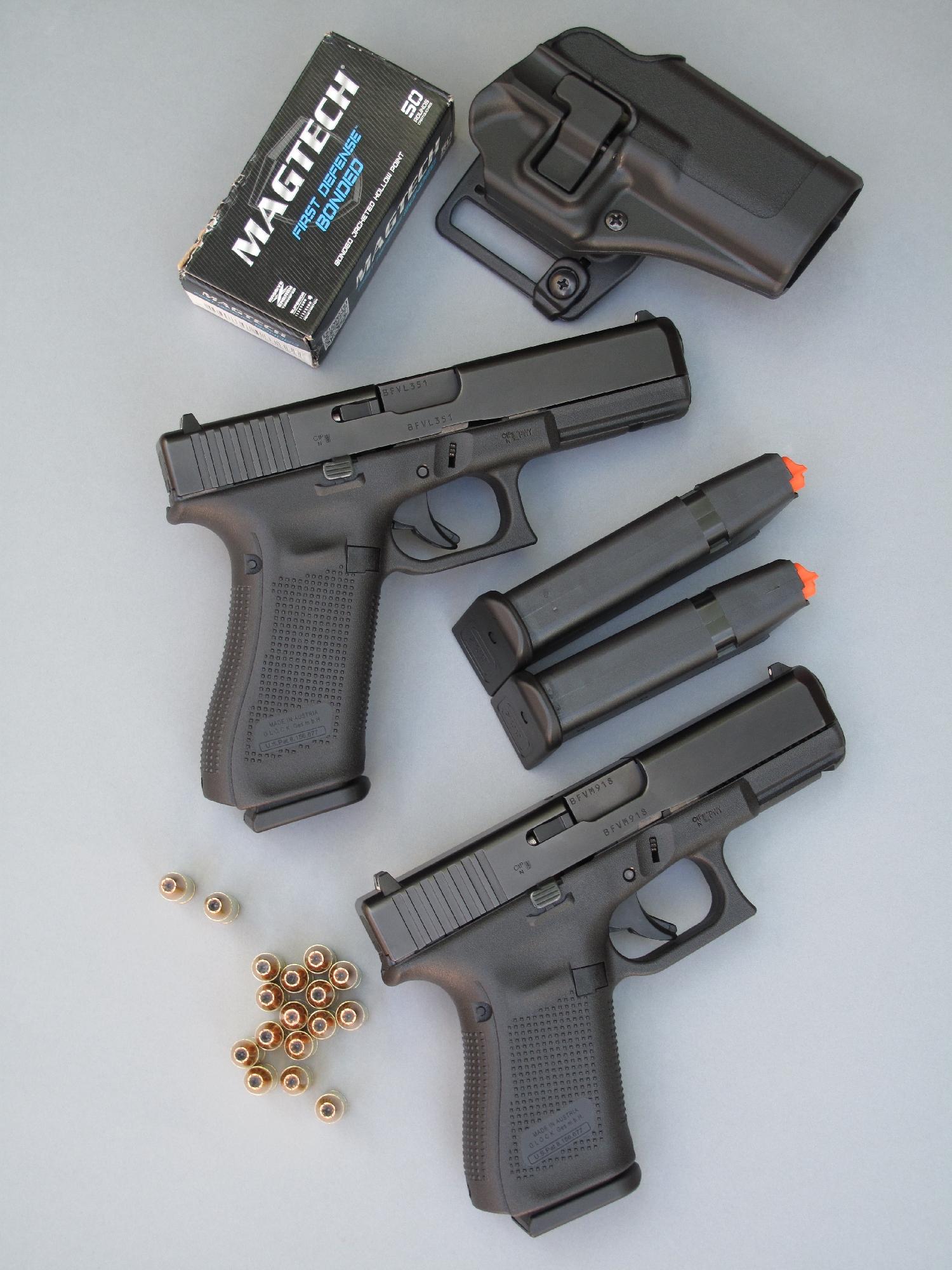 Les pistolets semi-automatiques Glock 17 Gen5 et Glock 19 Gen5 sont accompagnés ici par leurs chargeurs respectifs de 17 et 15 coups, par un holster à rétention « Serpa Concealment » de la firme américaine Blackhawk et par une boîte de 50 cartouches à balle blindée expansive « First Defense » de la firme brésilienne Magtech.