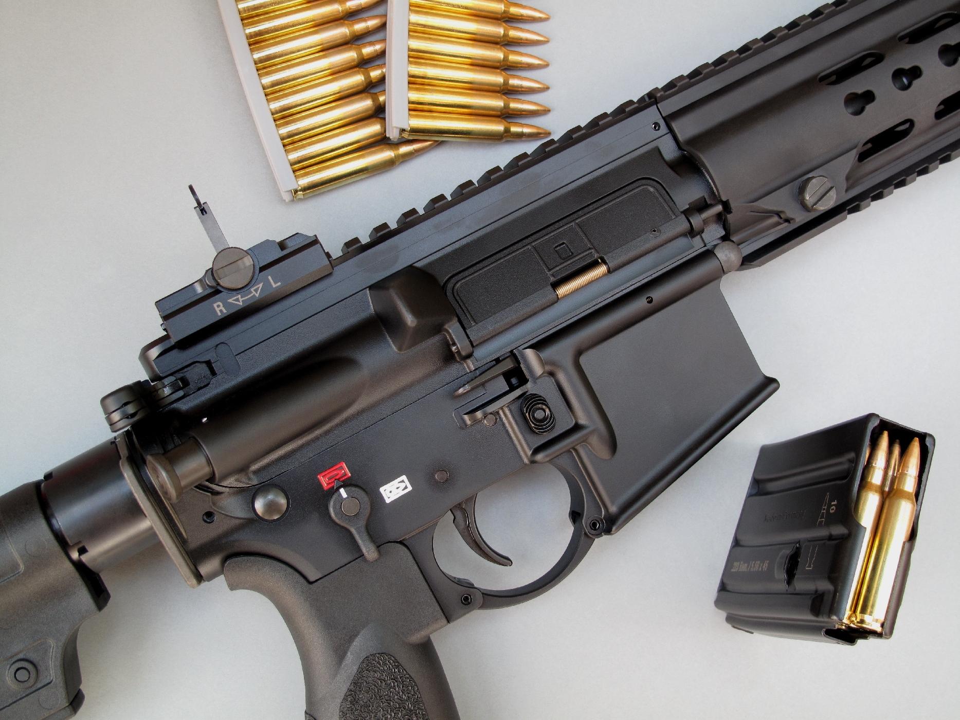 On notera la présence d'un poussoir d'aide au verrouillage (Forward Assist) et d'un volet de protection (Dust Cover) sur la fenêtre d'éjection, deux éléments directement issus du fusil d'assaut américain M16.